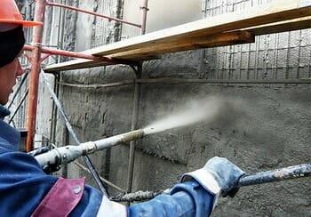 Нанесение слоя торкрета на стену